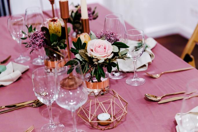 Gedeckter Hochzeitstisch rosa mit Blumen, Besteck