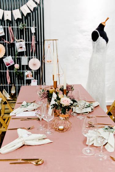 Gedeckter Tisch rosa mit Brautkleid im Hintergrund